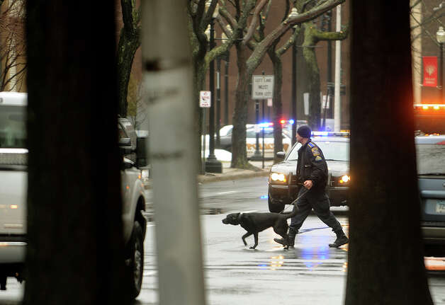 A police officer and dog head towards the Margaret E. Morton Government Center on State Street in downtown Bridgeport, where an inert explosive device was discovered on Wednesday, February 27, 2013. Photo: Brian A. Pounds / Connecticut Post