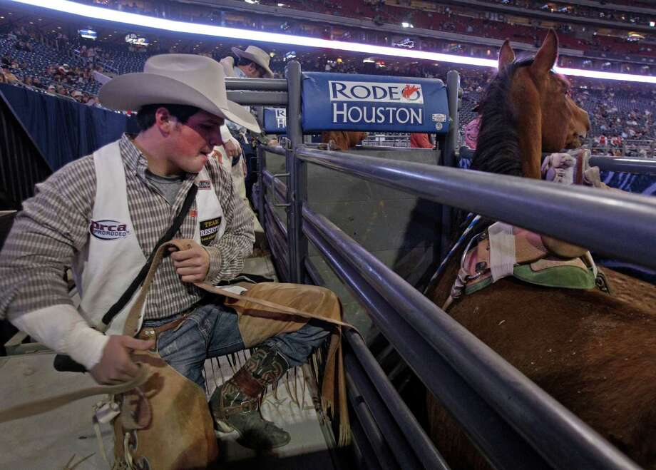 Bareback rider Richmond Champion of The Woodlands  attaches his rigging for his ride on bronc named Cool Water during RodeoHouston round two of Super Series I  at the Houston Livestock Show and Rodeo in Reliant Stadium Tuesday, Feb. 26, 2013, in Houston. Photo: Melissa Phillip, Houston Chronicle / © 2013  Houston Chronicle