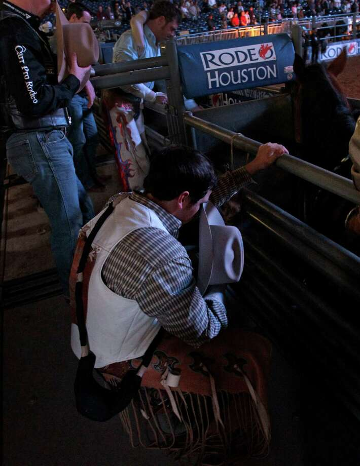 Bareback rider Richmond Champion of The Woodlands kneels in prayer during the invocation as he prepares for his ride on bronc named Cool Water during RodeoHouston round two of Super Series I. Photo: Melissa Phillip, Houston Chronicle / © 2013  Houston Chronicle