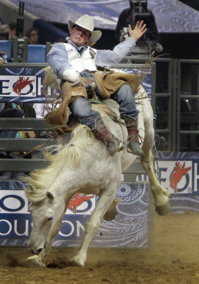 Richmond Champion of The Woodlands gets sideways during his bareback ride at RodeoHouston round one of Super Series I. Photo: Melissa Phillip, Houston Chronicle / © 2013  Houston Chronicle