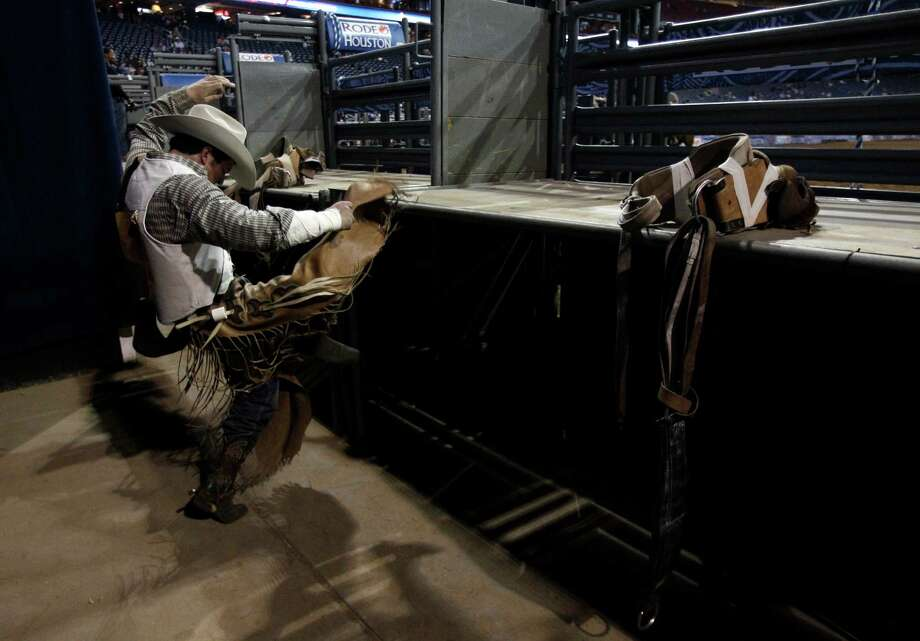 Bareback rider Richmond Champion of The Woodlands stretches behind the chutes as he prepares for his ride on bronc named Cool Water during RodeoHoustonround two of Super Series I. Photo: Melissa Phillip, Houston Chronicle / © 2013  Houston Chronicle