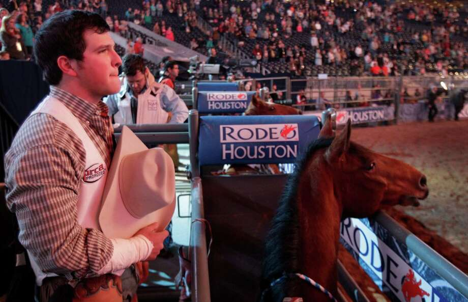 Bareback rider Richmond Champion of The Woodlands watches as red fireworks are displayed during the Nation Anthem salute as he prepares for his ride on bronc named Cool Water during RodeoHouston round two of Super Series I. Photo: Melissa Phillip, Houston Chronicle / © 2013  Houston Chronicle