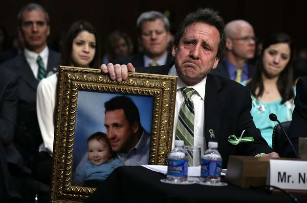 Neil Heslin, father of six-year-old Sandy Hook Elementary School shooting victim Jesse Lewis, holds a picture of him with Jesse as he testifies during a hearing before the Senate Judiciary Committee February 27, 2013 on Capitol Hill in Washington, DC. The committee held a hearing on The Assault Weapons Ban of 2013.