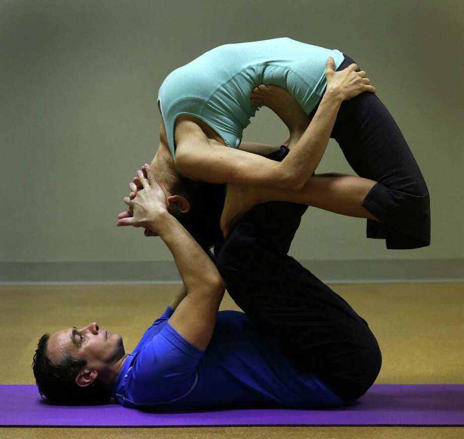 Acrobatics coach Vladimir Vladev trains a small group of committed yoga enthusiasts in AcroYoga, at Yoga Shala Studio, which combines acrobatics and Yoga, on Tuesday, Feb. 26, 2013. Vladev supports Ana Hollis, owner of Yoga Shala Studio, in a Flying Back Bend. Photo: Bob Owen, San Antonio Express-News / © 2012 San Antonio Express-News