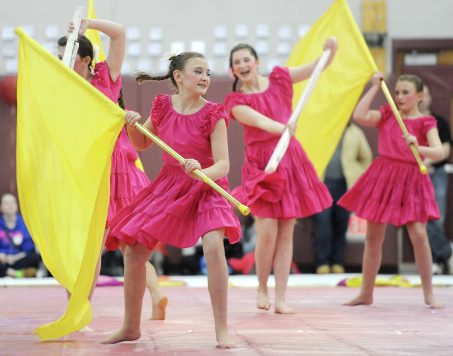 Shannon Burke, center, and Samantha Burke, right of center, perform with the Bethel High School junior varsity winter guard team at the Bethel Winterguard Home Show at Bethel High School in Bethel, Conn. Saturday, Feb. 23, 2013.  Twenty teams performed color guard routines at the event. Photo: Tyler Sizemore / The News-Times