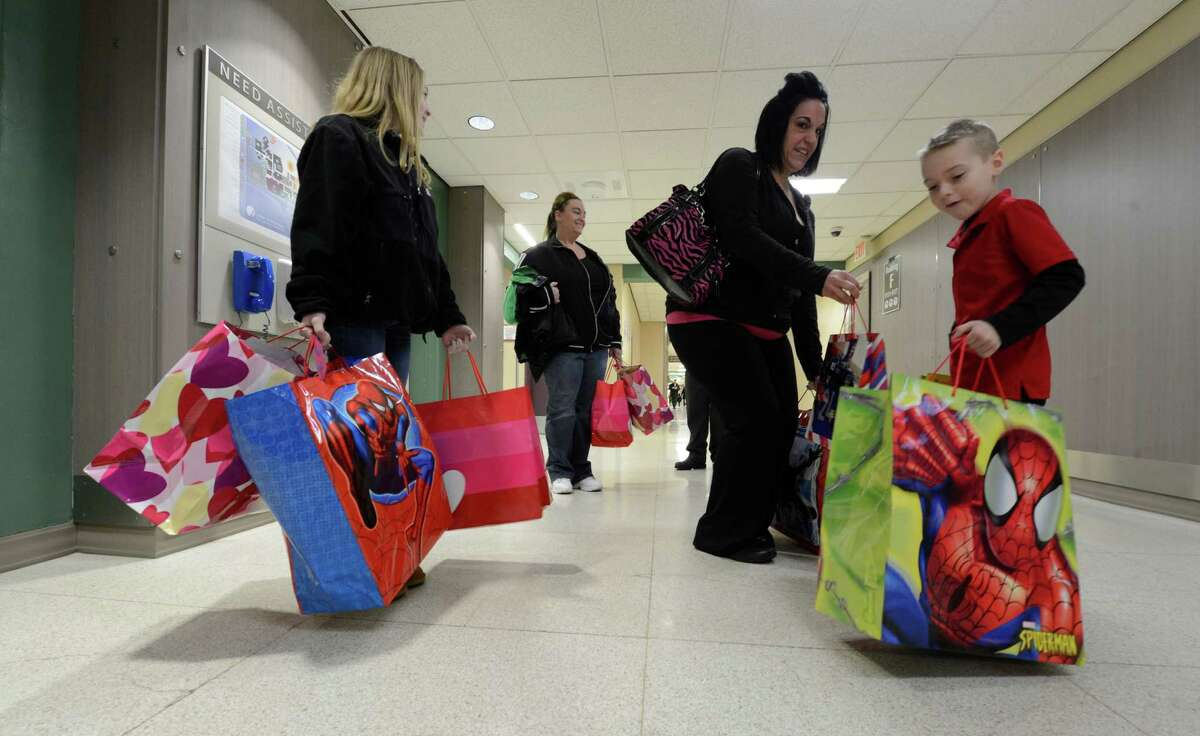 Dylan Romanowski, right carries toys for patients in the Melodies Center at the Albany Medical Center Feb. 27, 2013 in Albany, N.Y. Assisting with Dylan's class project is his sister, Makayla, left; aunt Tina Black and mom Karrie Romanowski, second from right. (Skip Dickstein/Times Union)