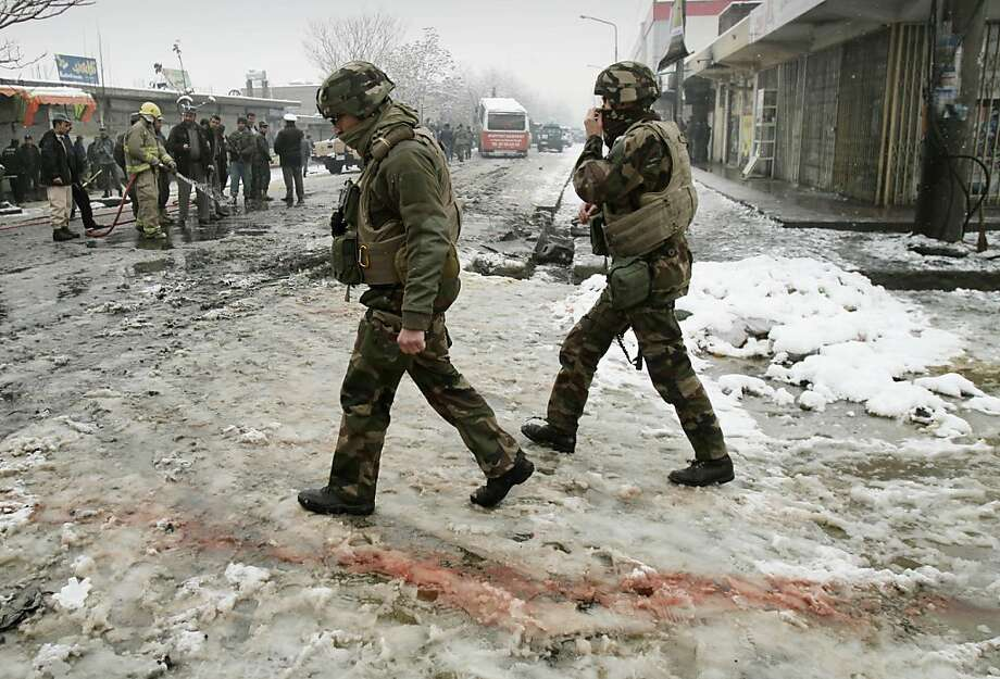 French soldiers with the NATO- led forces walk past blood stained snow at the scene of a suicide attack in Kabul, Afghanistan, Wednesday, Feb. 27, 2013. A man wearing a black overcoat and carrying an umbrella as a shelter against the heavy snow crossed a street in the Afghan capital early Wednesday morning toward an idling bus filled with Afghan soldiers, where he laid down and wiggled underneath. Then he exploded, engulfing the undercarriage of the bus in flames. Photo: Ahmad Jamshid, Associated Press