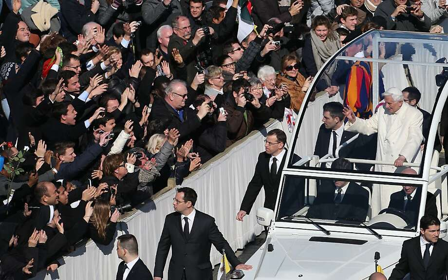 Pope Benedict waves from the popemobile to people gathered in St. Peter's Square for his final weekly public audience. He steps down from the papacy Thursday. Photo: Peter Macdiarmid, Getty Images