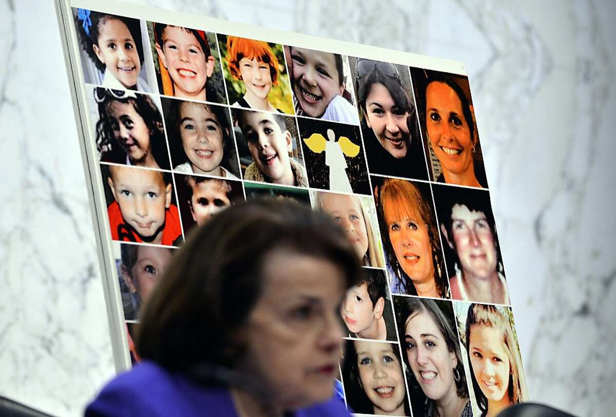 Pictures of Newtown's Sandy Hook Elementary School shooting victims are displayed as Senate Judiciary Committee chairperson Dianne Feinstein speaks during a hearing on