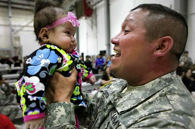 SFC Mario Orta of San Antonio lifts his daughter Lindsey Orta as members of the 449th Aviation Support Battalion of the Army National Guard participate in a mobilization ceremony at the Austin Army Aviation Support Facility on Wednesday, Feb. 27, 2013. Photo: Bob Owen, San Antonio Express-News / ©2013 San Antonio Express-News
