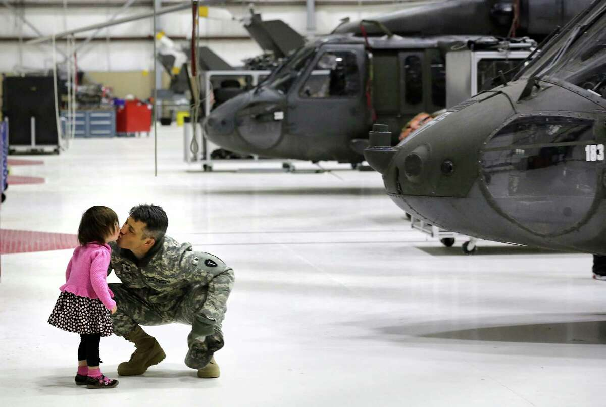 Lr. Col. James Nugent, of Austin, gets a kiss from his daughter, Sienna, before his deployment to Iraq.