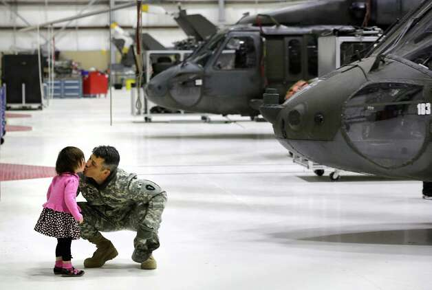 Lr. Col. James Nugent, of Austin, gets a kiss from his daughter, Sienna, before his deployment to Iraq. Photo: Bob Owen, San Antonio Express-News Photo: Bob Owen, San Antonio Express-News / ©2013 San Antonio Express-News