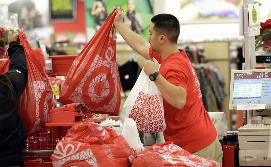FILE - In this Nov. 23, 2012 file photo, a Target employee hands bags to a customer at the register at a Target store in Colma, Calif. Target's fiscal fourth-quarter net income dipped 2 percent as it dealt with intense competition during the crucial holiday season. But its adjusted results beat analysts' estimates and it forecast first-quarter earnings above Wall Street's view. (AP Photo/Jeff Chiu, File) Photo: Jeff Chiu