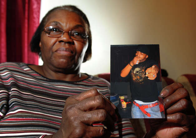 Gloristine Thomas holds a photo of her son Greg at her home on Howard Avenue in Bridgeport, Conn. on Wednesday February 27, 2013. Greg was shot and killed in front of the Howard Avenue home on January 1, 2012. Eventually the three rings he was wearing in the photo disappeared with denials from St. Vincent's Hospital and the Bridgeport police Department that they have them. Photo: Christian Abraham / Connecticut Post