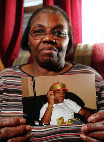 Gloristine Thomas holds a photo of her son Greg at her home on Howard Avenue in Bridgeport, Conn. on Wednesday February 27, 2013. Greg was shot and killed in front of the Howard Avenue home on January 1, 2012. Eventually the rings he was wearing in the photo, plus another not shown, disappeared with denials from St. Vincent's Hospital and the Bridgeport police Department that they have them. Photo: Christian Abraham / Connecticut Post