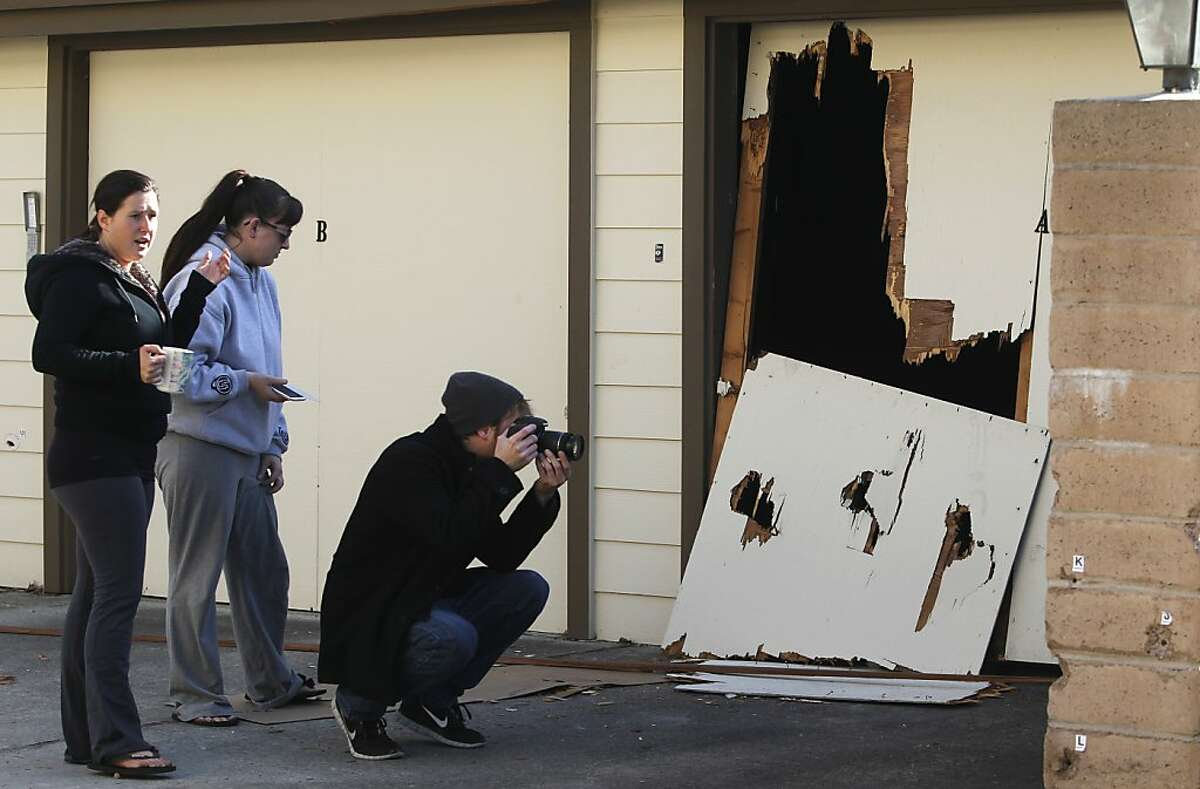 Misha Lamberson (left), Megan Fulton (center) and Chris Renfer visit the scene, on Doyle Street in Santa Cruz, Calif. on Wednesday, Feb. 27, 2013, where police officers shot and killed Jeremy Peter Goulet Tuesday after he gunned down two Santa Cruz officers a short distance away.