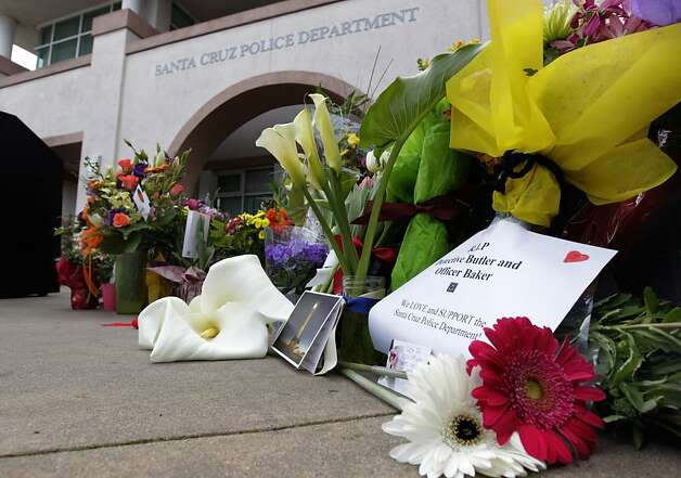 "Flowers at police headquarters honor the memory of Detec- tive Sgt. Loran ""Butch"" Baker and Detective Elizabeth Butler. Photo: Paul Chinn, The Chronicle"