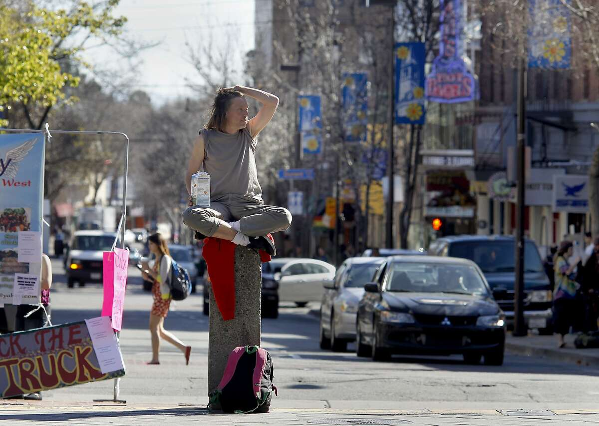 At the intersection of Telegraph Avenue and Bancroft, a man sat on a concrete post and urged pedestrians to think more about the poor environment Tuesday February 26, 2013. The city of Berkeley, Calif. will hold a community meeting to discuss what residents want to do about Telegraph Avenue. Officials say that students don't shop or socialize there as much as in the past.