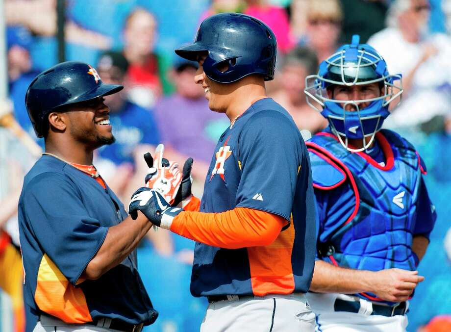 Astros center fielder George Springer, center, celebrates his two-run home run with Astros second baseman Delino Deshields, left, as Blue Jays catcher J.P. Arencibia, right, watches during the fifth inning. Photo: Nathan Denette