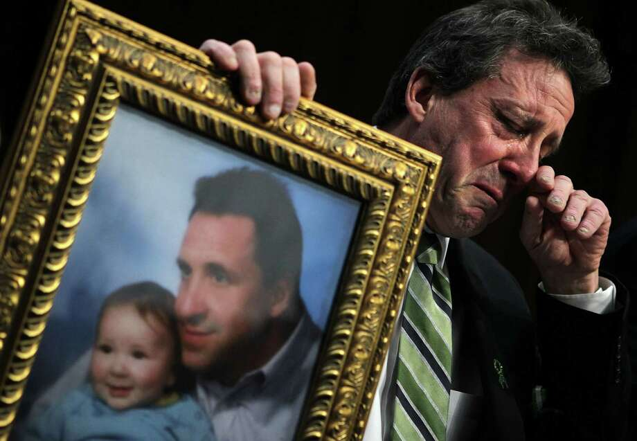 """WASHINGTON, DC - FEBRUARY 27:  Neil Heslin, father of six-year-old Sandy Hook Elementary School shooting victim Jesse Lewis, holds a picture of him with Jesse as he testifies during a hearing before the Senate Judiciary Committee February 27, 2013 on Capitol Hill in Washington, DC. The committee held a hearing on """"The Assault Weapons Ban of 2013.""""  (Photo by Alex Wong/Getty Images) Photo: Alex Wong, Getty Images / 2013 Getty Images"""