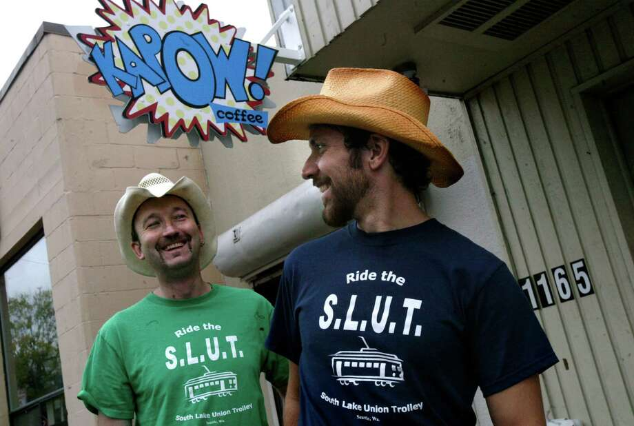 "4. Kapow! Coffee was known for its ""Ride the S.L.U.T."" T-shirts, which poked fun at the original name of the neighborhood's streetcar, the ""South Lake Union Trolley."" But it was really a jab at gentrification. Here's T-shirts creators Jerry Thomson, right, and Don Clifton. Photo: ANDY ROGERS/Seattle Post-Intelligencer, SEATTLE POST-INTELLIGENCER / SEATTLE POST-INTELLIGENCER"