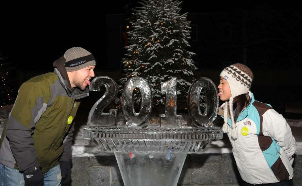Chris Scott, 30 on the left and Jackie Scott, 28, both from Jacksonville, N.C. visiting tried their luck at the Danbury First Night celebration on Thursday Dec. 31, 2009 by touching their tongues to the freshly carved 2010 ice sculpture in the court yard of the Danbury Public Library.