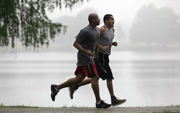 David Banks (left) and Joe Amaro take to the fog as they run laps around Woodlawn Lake. Photo: Express-News File Photo