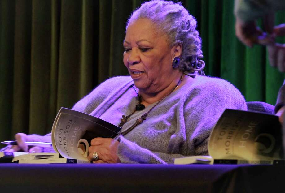 "Author Toni Morrison signs copies of her latest book ""Home,"" during Google's online program series, Authors At Google, on Wednesday, Feb. 27, 2013 in New York.  (AP Photo/Bebeto Matthews) Photo: Bebeto Matthews"