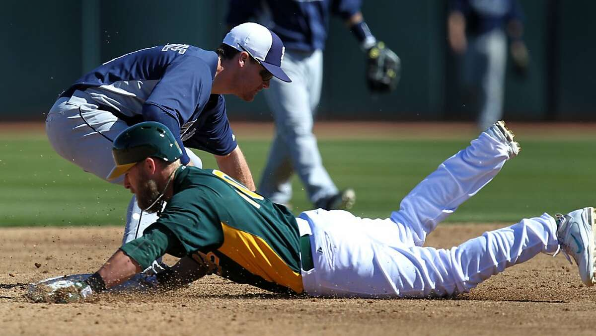 Oakland Athletics Daric Barton slides safely into second base in front of San Diego Logan Forsythe Wednesday, Feb. 27, 2013, during their exhibition spring training baseball game in Phoenix, Ariz.