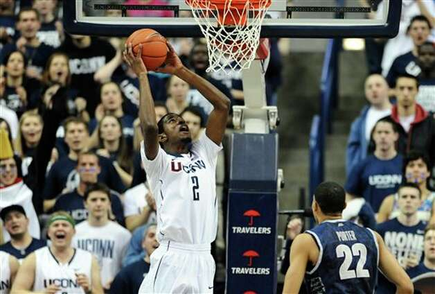 Connecticut's DeAndre Daniels lines up a dunk as Georgetown's Otto Porter Jr. (22) watches during the first half of an NCAA college basketball game in Storrs, Conn., Wednesday, Feb. 27, 2013. (AP Photo/Jessica Hill)