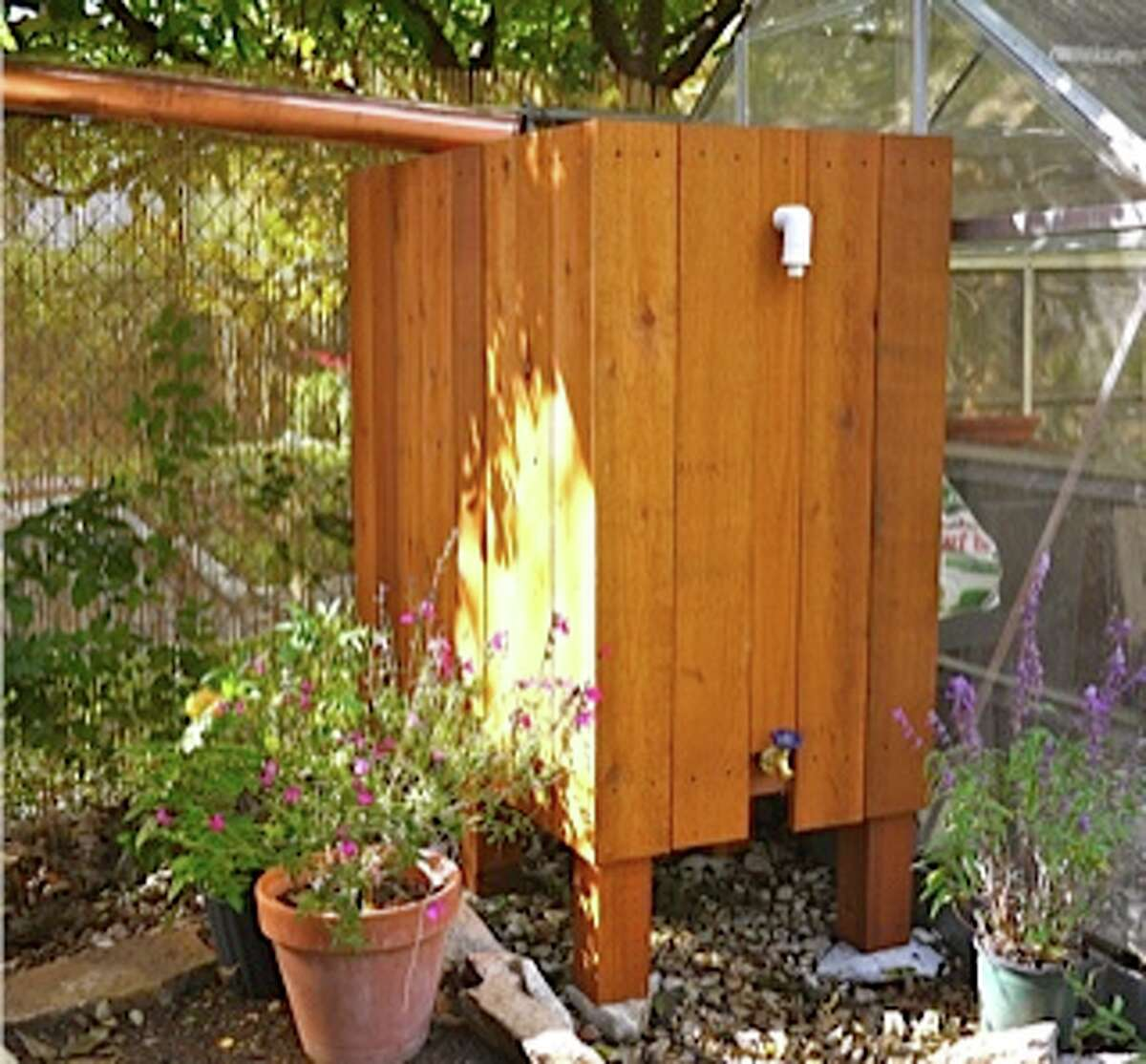 Two 55-gallon drums hidden behind cedar boards collect rainwater off a roof for landscape watering.