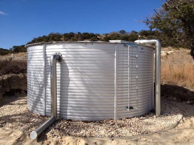 A 10,000-gallon galvanized metal tank will collect and store rainwater for household use. Photo: Courtesy One Texas Water