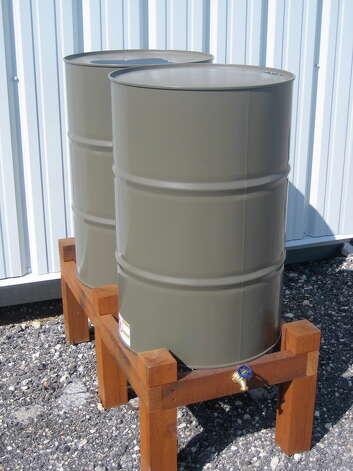 A simple rainwater collection system of two 55-gallon drums can store rainwater for plant irrigation. Photo: Courtesy One Texas Water
