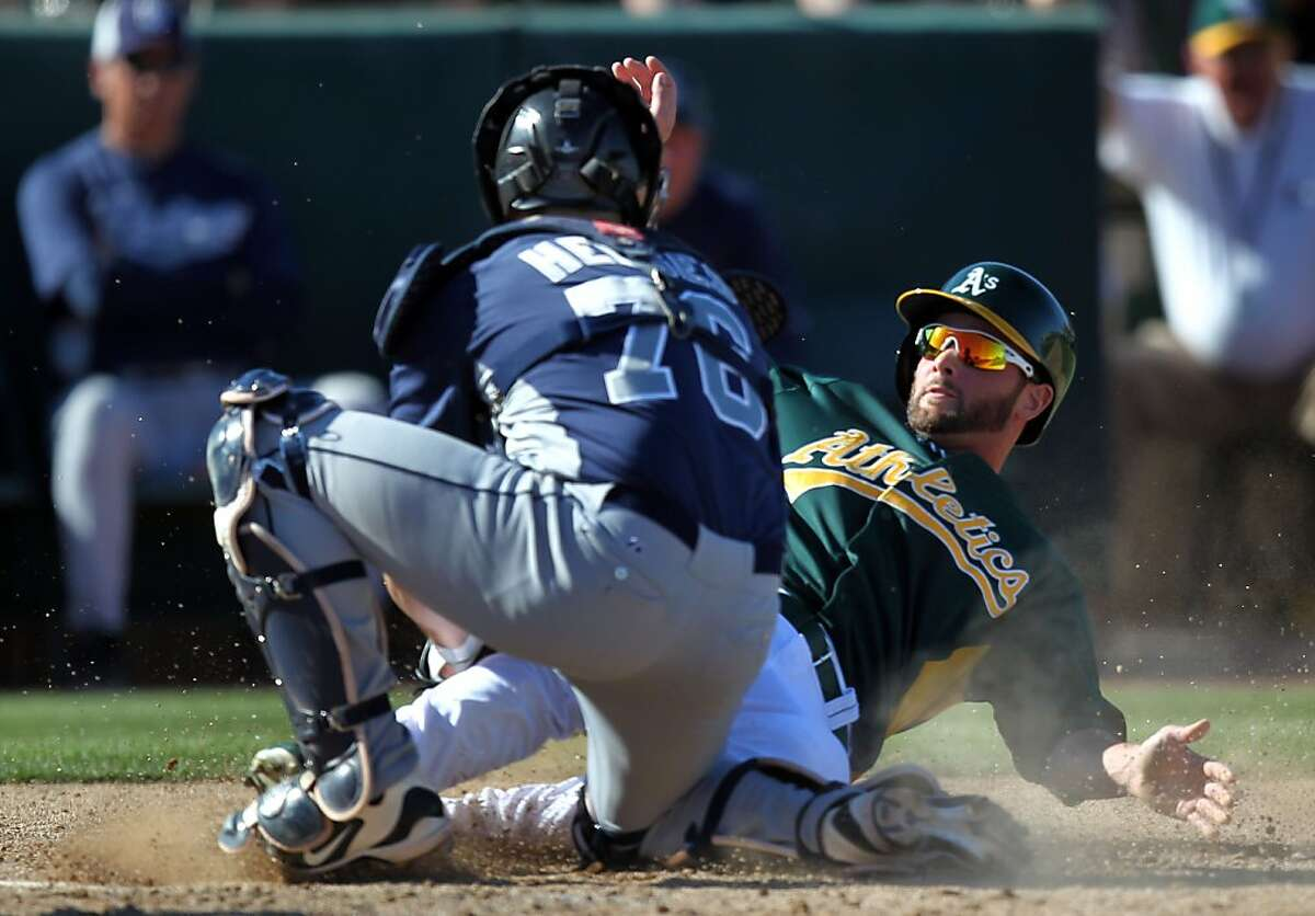 Oakland Athletics Andy Parrino slides into home plate as San Diego Padres catcher Austin Hedges tags him out Wednesday, Feb. 27, 2013, during their exhibition spring training baseball game in Phoenix, Ariz.