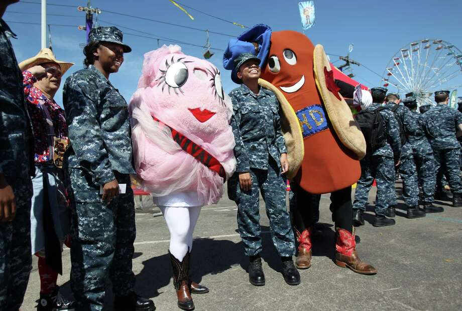 Seaman Recruit Christie Cutter and Hospital Men Lauren Hawkins pose for a photo with Ms. Carnival and Howdy Dog as they wait in line at the Hide Out to eat lunch on Armed Forces Appreciation Day at the Houston Livestock Show & Rodeo on Wednesday, Feb. 27, 2013, in Houston. Photo: Mayra Beltran, Houston Chronicle / © 2013 Houston Chronicle