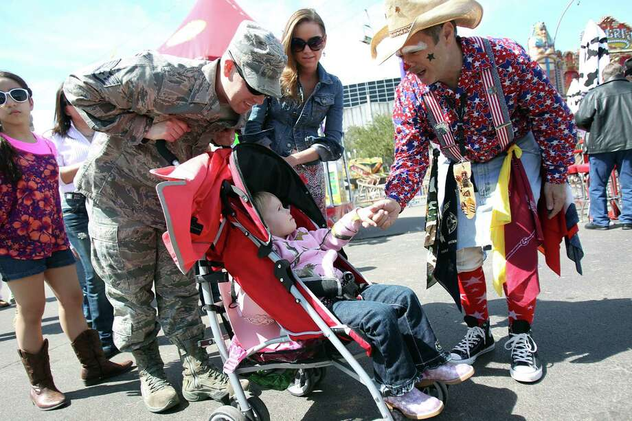 Joshua Mathews and his wife Hunter Mathews smile as their daughter Keridon Mathews, 2, is greeted by Rodeo Clown 'Stars' Glenn Bishop on Armed Forces appreciation day at the Houston Livestock Show & Rodeo on Wednesday, Feb. 27, 2013, in Houston. Photo: Mayra Beltran, Houston Chronicle / © 2013 Houston Chronicle