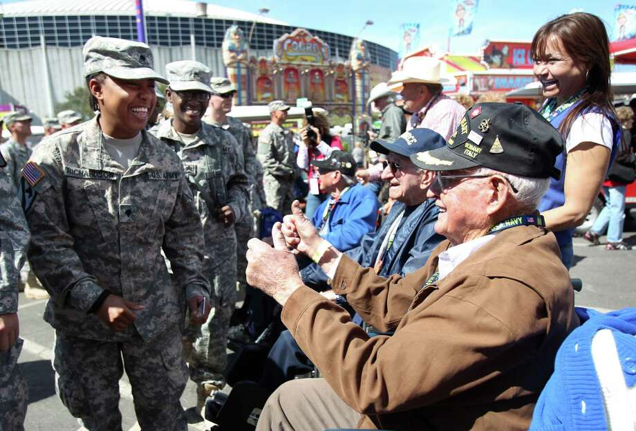Spc. Michelle Richardson smiles at Roy Hughes, WWII U.S. Army Veteran, as troops enter the Hideout for a warm lunch on Armed Forces appreciation day at the Houston Livestock Show & Rodeo on Wednesday, Feb. 27, 2013, in Houston. Photo: Mayra Beltran, Houston Chronicle / © 2013 Houston Chronicle