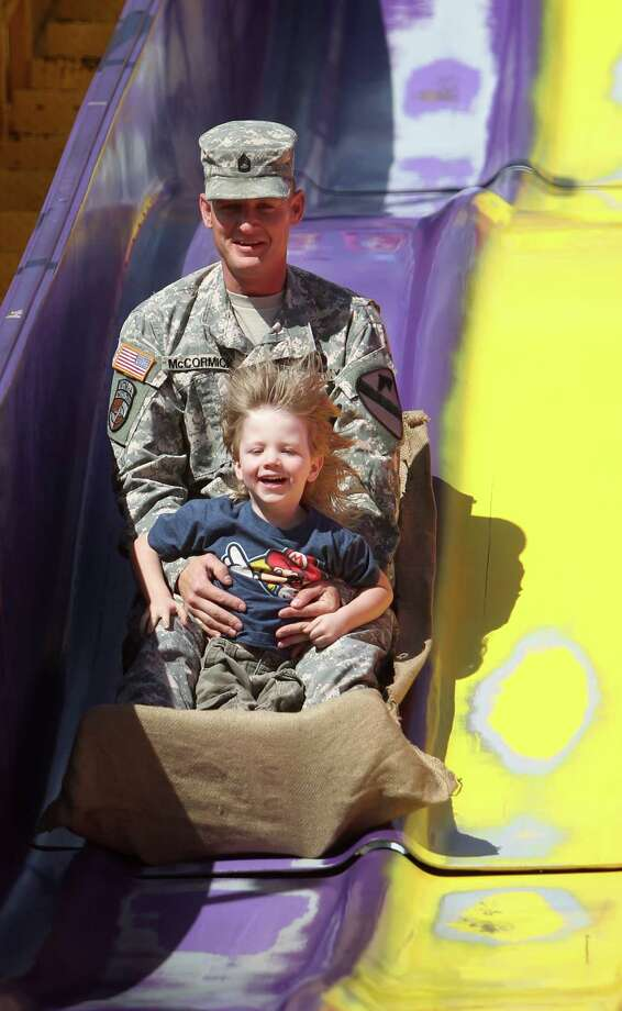 SFC Richard McCormick holds on to his son Wyatt McCormick as they ride the 'Super Slide' on Armed Forces Appreciation Day. Photo: Mayra Beltran, Houston Chronicle / © 2013 Houston Chronicle