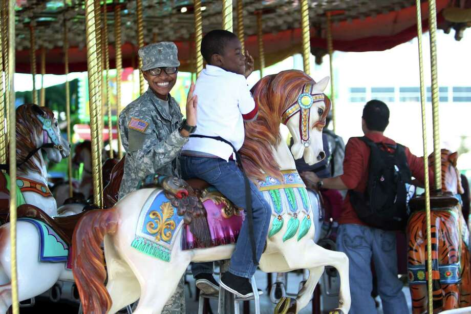2LT Chassidi Reese smiles while riding the carousel with Caiden Smith, step-son, during Armed Forces Appreciation Day. Photo: Mayra Beltran, Houston Chronicle / © 2013 Houston Chronicle