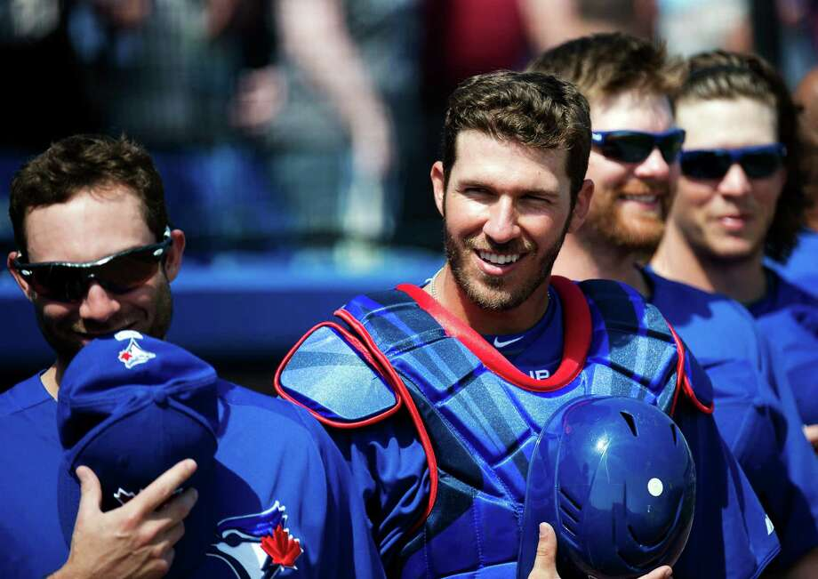Everyone needs spring training, especially the singer who botched the lyrics to the U.S. and Canadian national anthems before Wednesday's game and drew laughter from catcher J.P. Arencibia, right, and other Blue Jays players. Photo: Nathan Denette, SUB / The Canadian Press