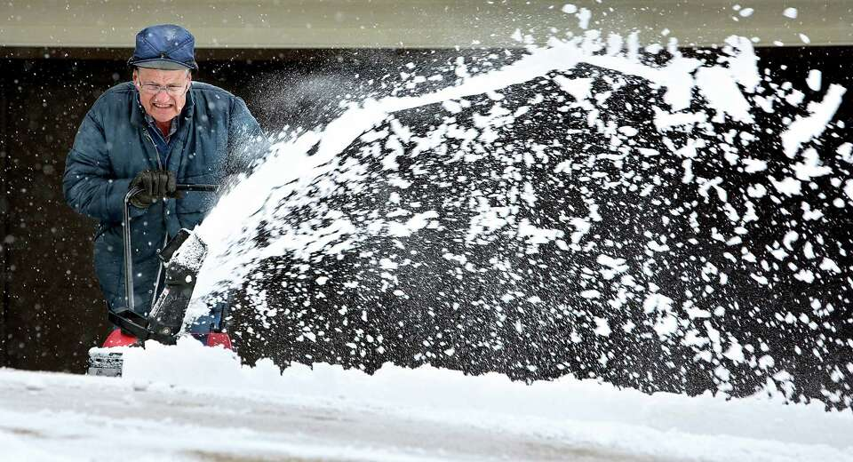 Lavern Heitzman throws snow from his driveway along Rush Street in Dubuque, Iowa during a snowfall W