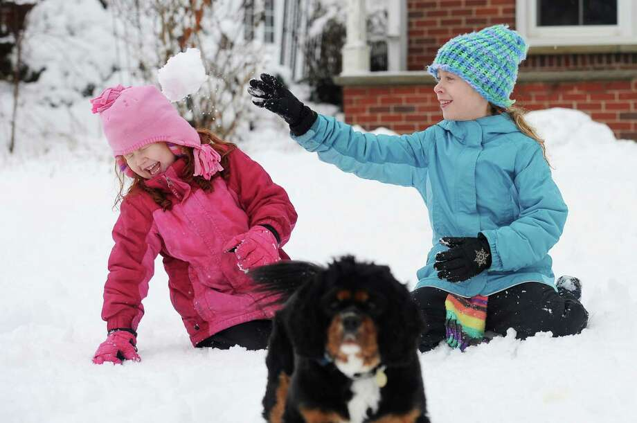 Six-year-old Jaylee Oeschger, 6, laughs as she is hit in the head with a snowball thrown by her sister Ileana, 10, as they play in the snow with their dog Mavis on Wednesday, Feb. 27, 2013 in Ann Arbor, Mich. Photo: Melanie Maxwell, Associated Press / AnnArbor.com