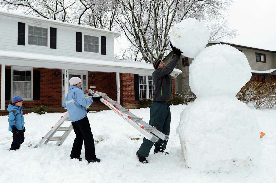Brandon Rink, 6, watches as his mother Susan holds a ladder as his father David pushes the head of their giant snowman into place on Wednesday, Feb. 27, 2013 on Glen Leven Road in Ann Arbor, Mich. The family, along with siblings Justin, 8 and Chloe, 3, started building the snowman the night before creating the base out snow from the driveway. Photo: Melanie Maxwell, Associated Press / AnnArbor.com