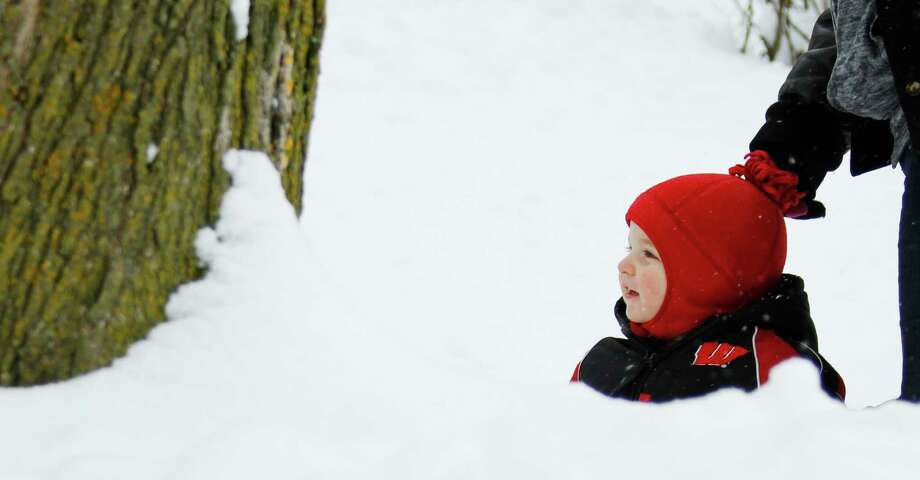 Dakota Roltgen, 1, of West Bend is able to see over the snow hill created by snow plows in West Bend, Wis., on Wednesday, Feb. 27, 2013. Snow is expected to continue through Wednesday night. Photo: John Ehlke, Associated Press / The Daily News