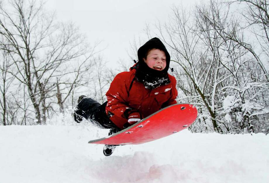 Luke Moris, 11, of the Town of Farmington smiles as he is airborne after hitting a jump on the sledding hill in Ridge Run Park in West Bend, Wis., on Wednesday, Feb. 27, 2013. Snow is expected to continue through Wednesday night. Photo: John Ehlke, Associated Press / The Daily News