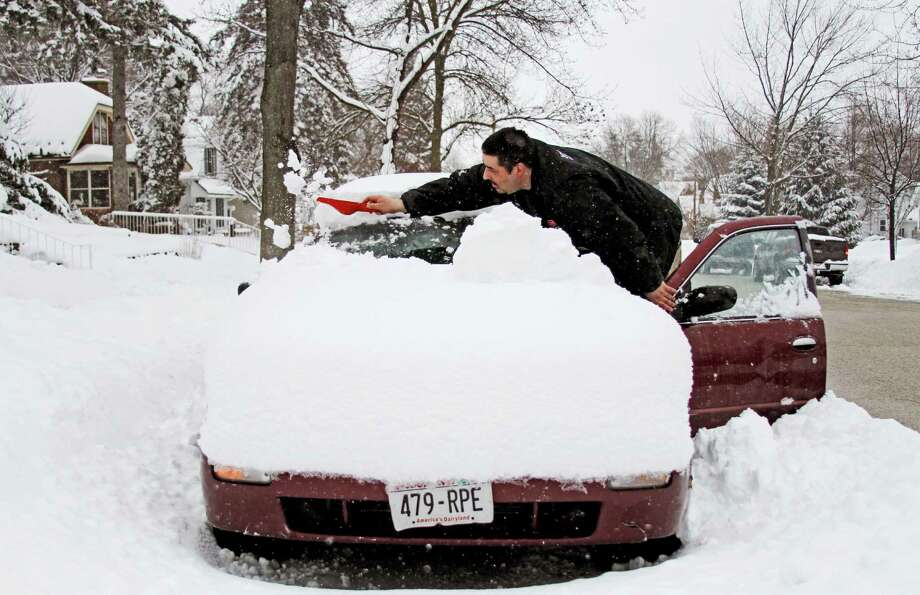 Neil Zweck of West Bend cleans the front of his car off with a dust pan while attempting to get hi scar uncovered in West Bend, Wis., on Wednesday, Feb. 27, 2013. Zweck's garage was full with items as he plans to move on Friday and had to park his car on the street the night before.  Snow is expected to continue through Wednesday night. Photo: John Ehlke, Associated Press / The Daily News