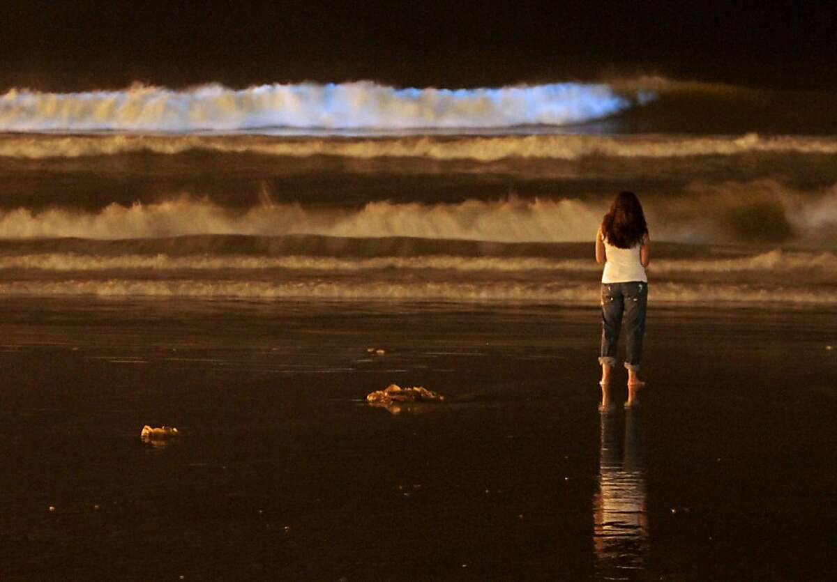 A visitor to Oceanside Pier Beach watches the spectacular flashes of neon blue in the crashing waves caused by an intense late-season red tide on Sept. 29, 2011 in Oceanside, Calif. The phenomenon known as bioluminescence is caused when algae cells are jostled in the waves. Red tide is a concentrated algae bloom which discolors the water and looks dark red in the daytime. (AP Photo/Los Angeles Times, Don Bartletti) NO FORNS; NO SALES; MAGS OUT; ORANGE COUNTY REGISTER OUT; LOS ANGELES DAILY NEWS OUT; VENTURA COUNTY STAR OUT; INLAND VALLEY DAILY BULLETIN OUT; SAN BERNARDINO SUN OUT; MANDATORY CREDIT, TV OUT
