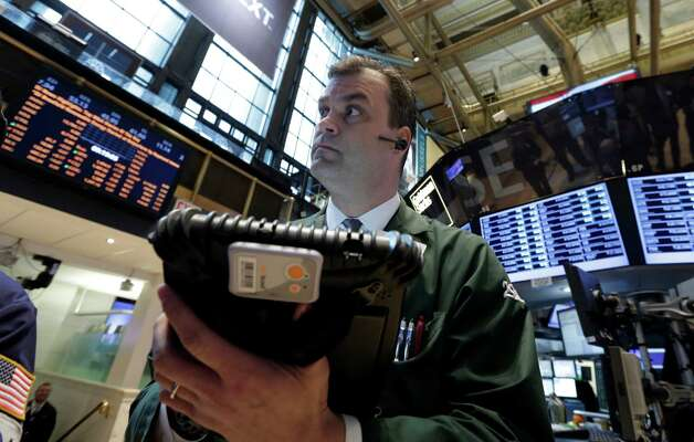 In this Tuesday, Feb. 26, 2013, photo,  Trader William Lawrence works on the floor of the New York Stock Exchange.Futures are rising as Chairman Ben Bernanke heads to Capitol Hill to explain what the Federal Reserve will do to accelerate the economic recovery.  (AP Photo/Richard Drew) Photo: Richard Drew