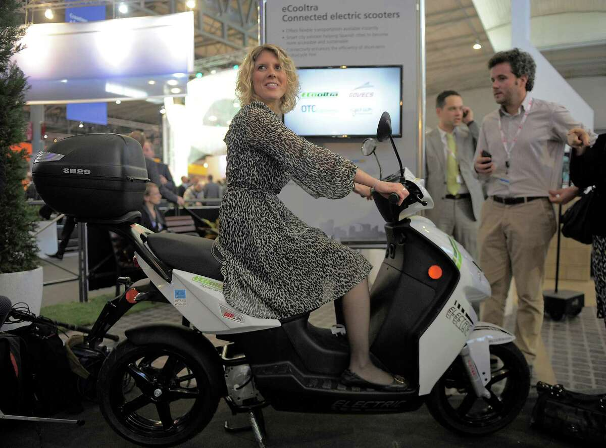 In this Tuesday, Feb. 26, 2013, photo, a woman sits on an eCooltra Connected electric scooters at the Mobile World Congress, the world's largest mobile phone trade show, in Barcelona, Spain. The first wave of the wireless revolution was getting people to talk to each other through cellphones. The second, it seems, will be getting things to talk to each other, with no human intervention: cars that talk to your insurance company?'s computers, bathroom scales that talk to your phone, and electric meters that talk to your air conditioners. So-called machine-to-machine technology all the buzz at this year?'s largest wireless trade show, and some analysts believe these types of connection will outgrow the traditional phone business in less than a decade. (AP Photo/Manu Fernandez)