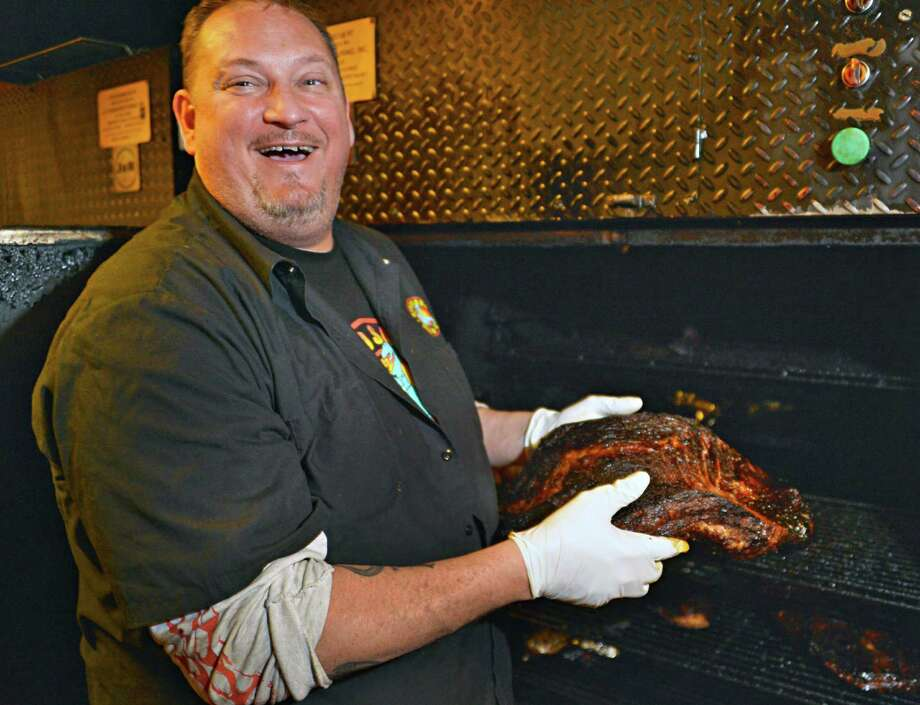 "Head chef for the Dinosaur Bar-B-Que chain Jeff ""Cooter"" Coon takes a briscut from an Oyler barbecue pit at their Troy location Wednesday Feb. 27, 2013.  (John Carl D'Annibale / Times Union) Photo: John Carl D'Annibale / 00021326A"